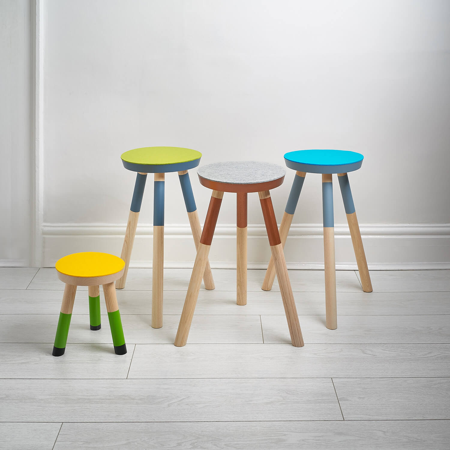 Studio product photograph of handmade vividly painted stools