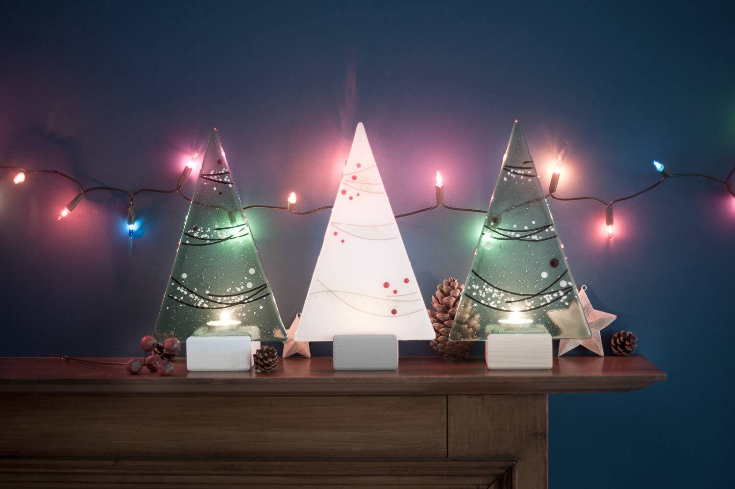 Glassware maker's Christmas trees photographed on the mantlepiece