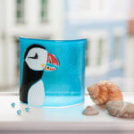 Puffin curve piece of glass art photographed with seashore props with old buildings in the background out of focus