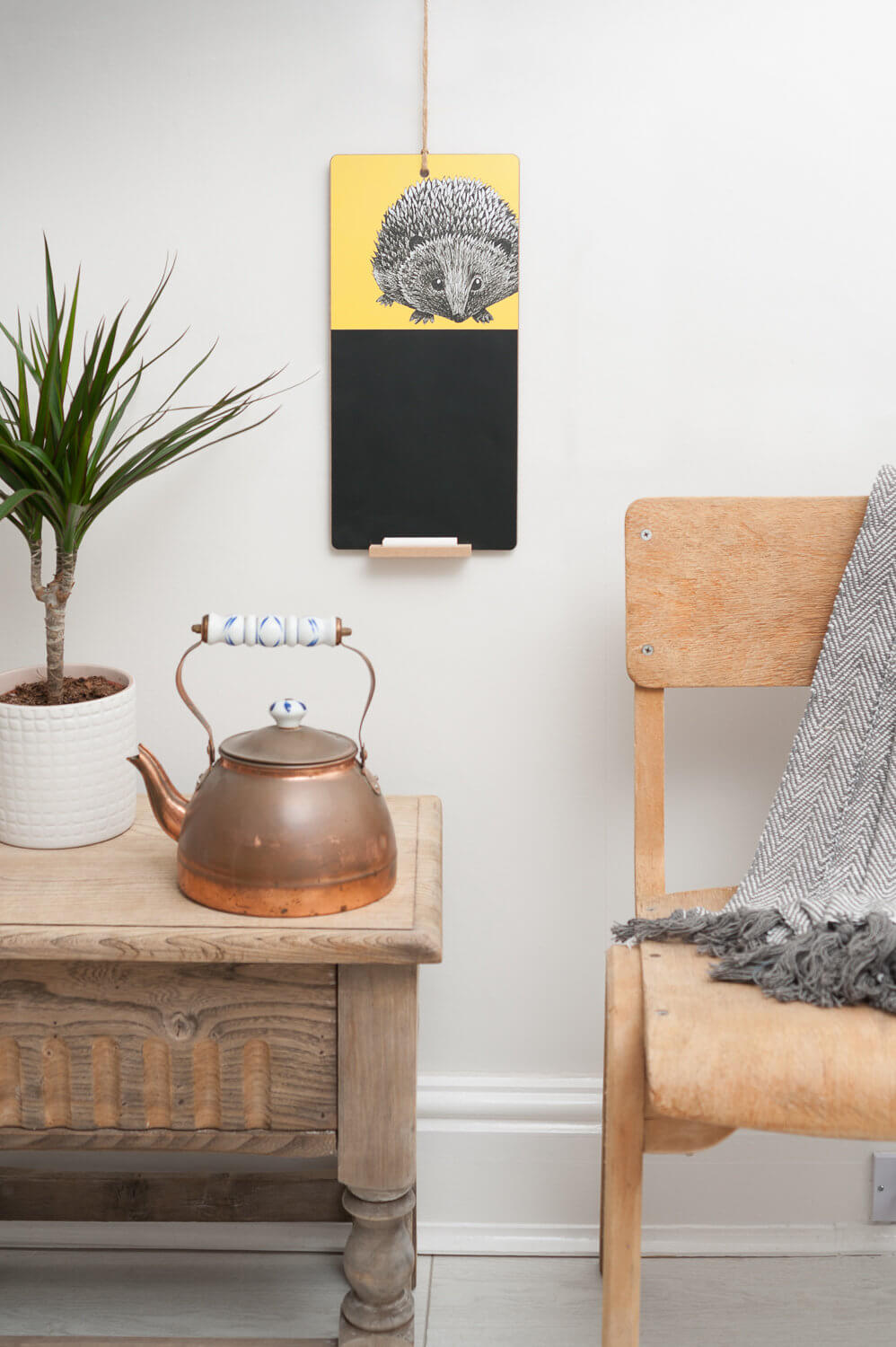 Designers Perkins and Morley lifestyle product photograph showing hedgehog chalkboard with rustic furniture