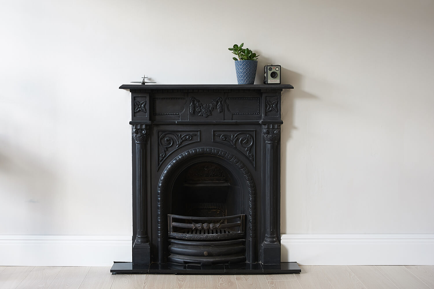 The studio's cast iron fireplace, with a few props on the mantlepiece