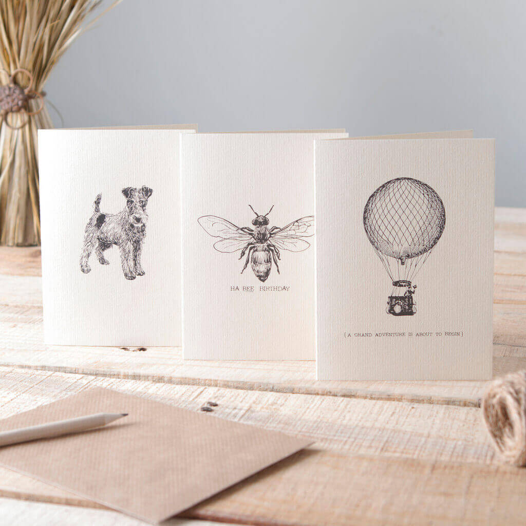 Three greetings cards photographed and styled in a rustic setting