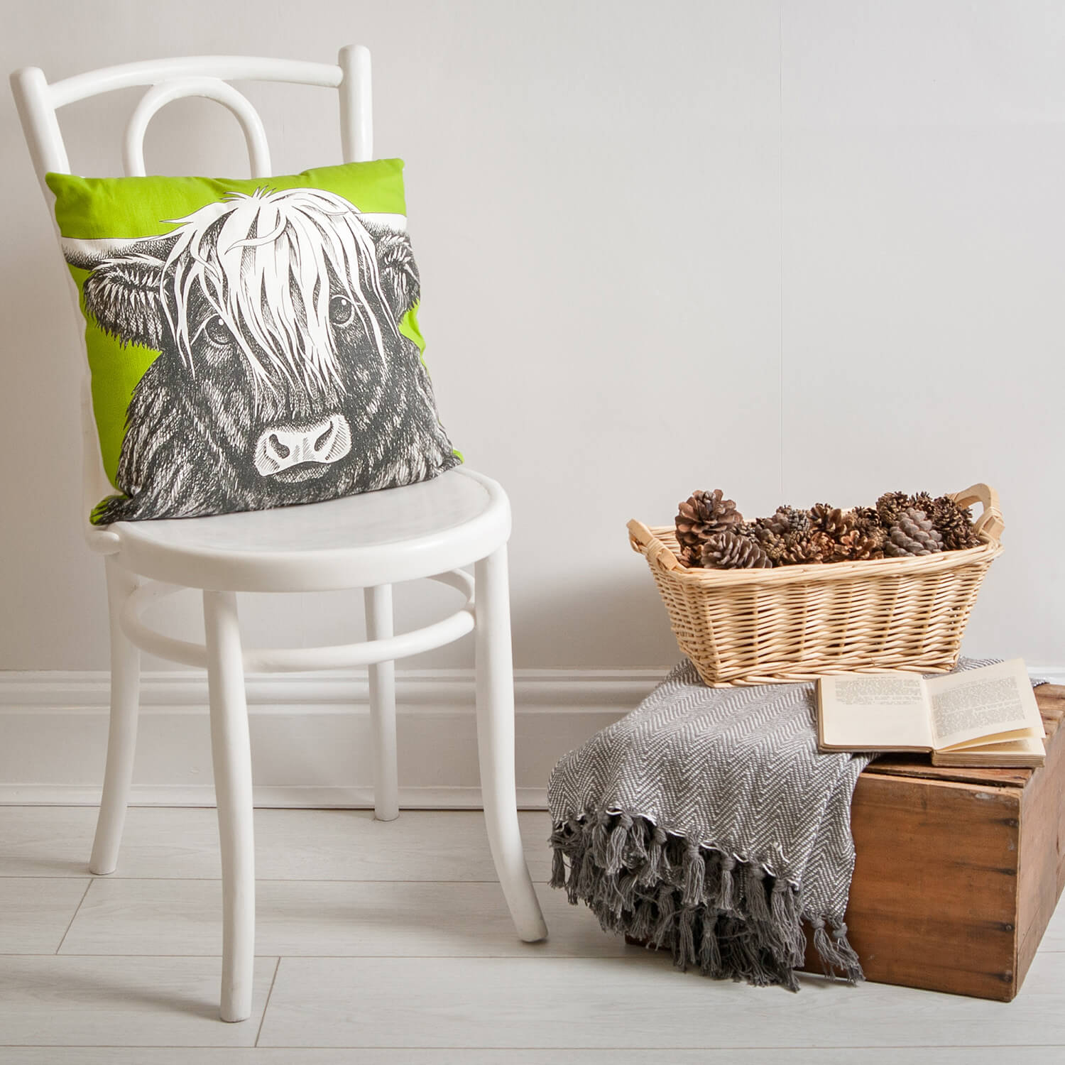Green printed cushion of a highland cow photographed in a lifestyle setting