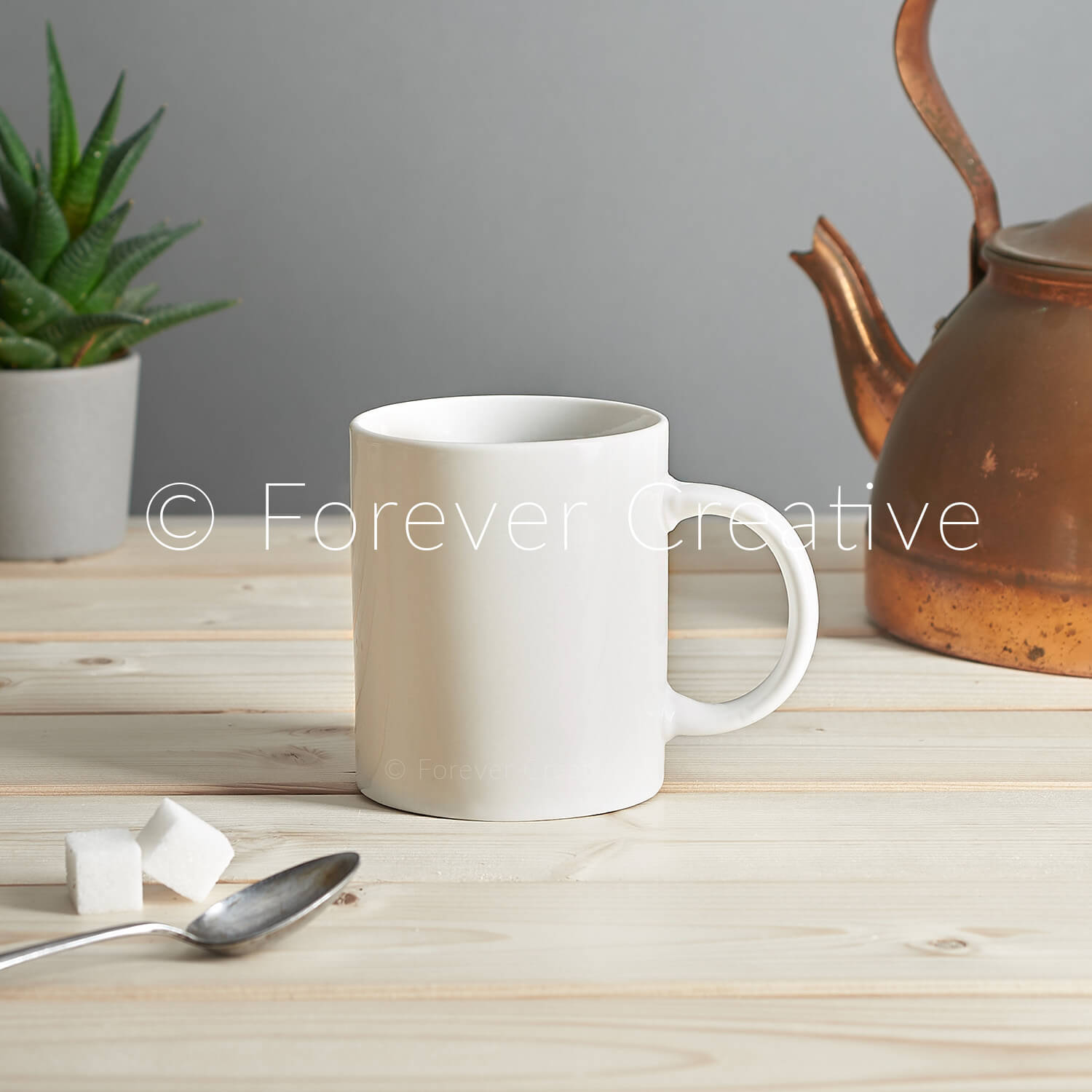 Stock photography of a ceramic white mug in a setting with old kettle, ready for designer to superimpose their artwork into