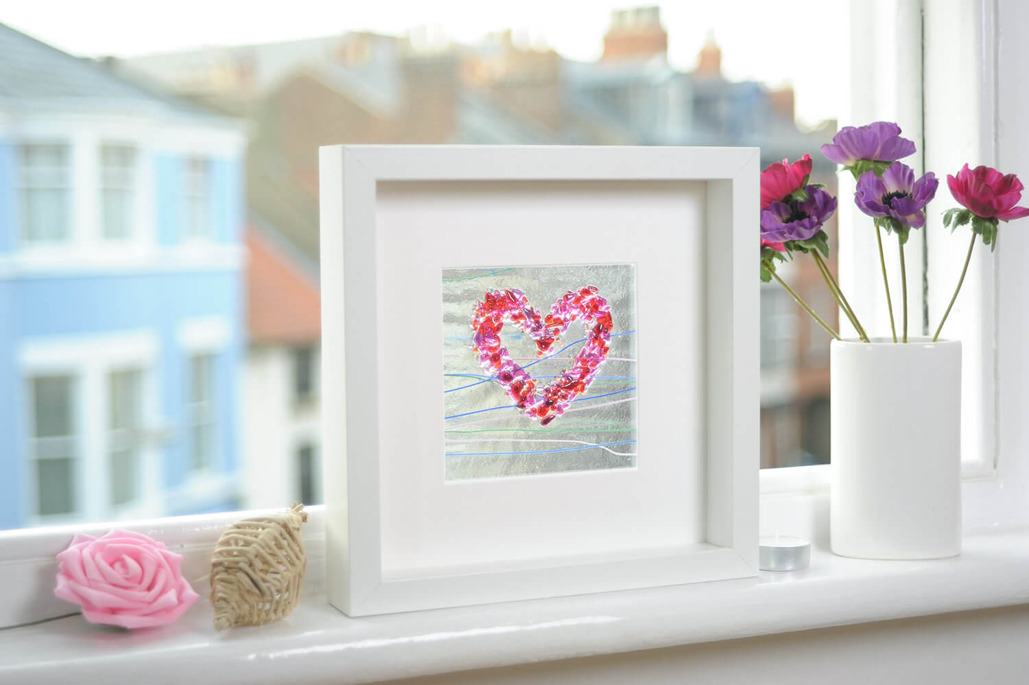 Framed glass art photographed on the window sill with period buildings in the background out of focus