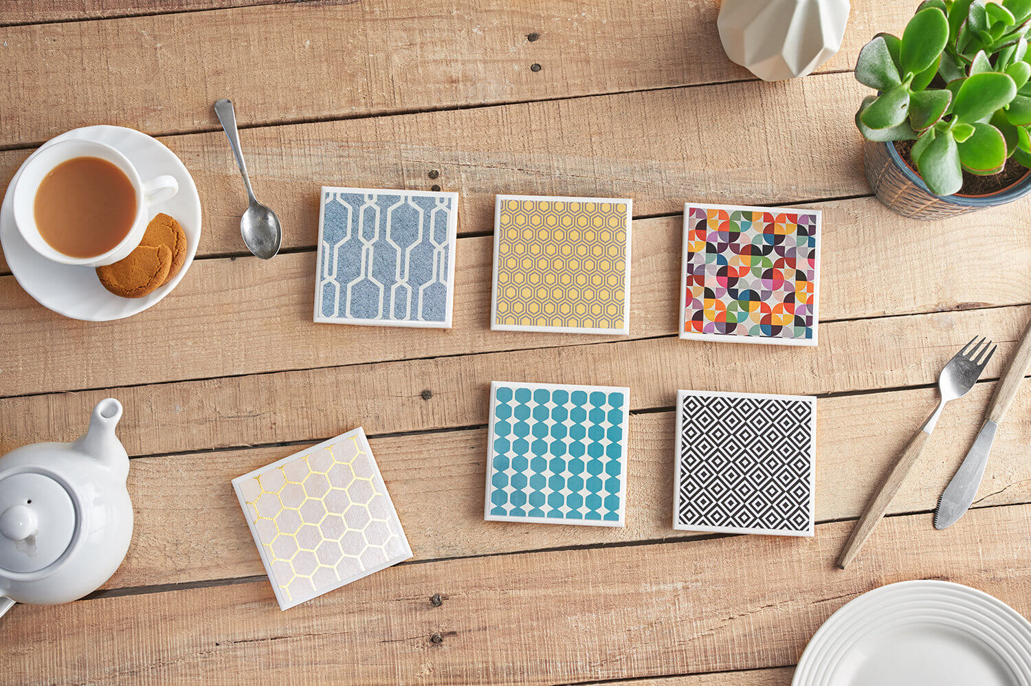 Overhead flatlay product photography of geometric coasters with associated lifestyle props