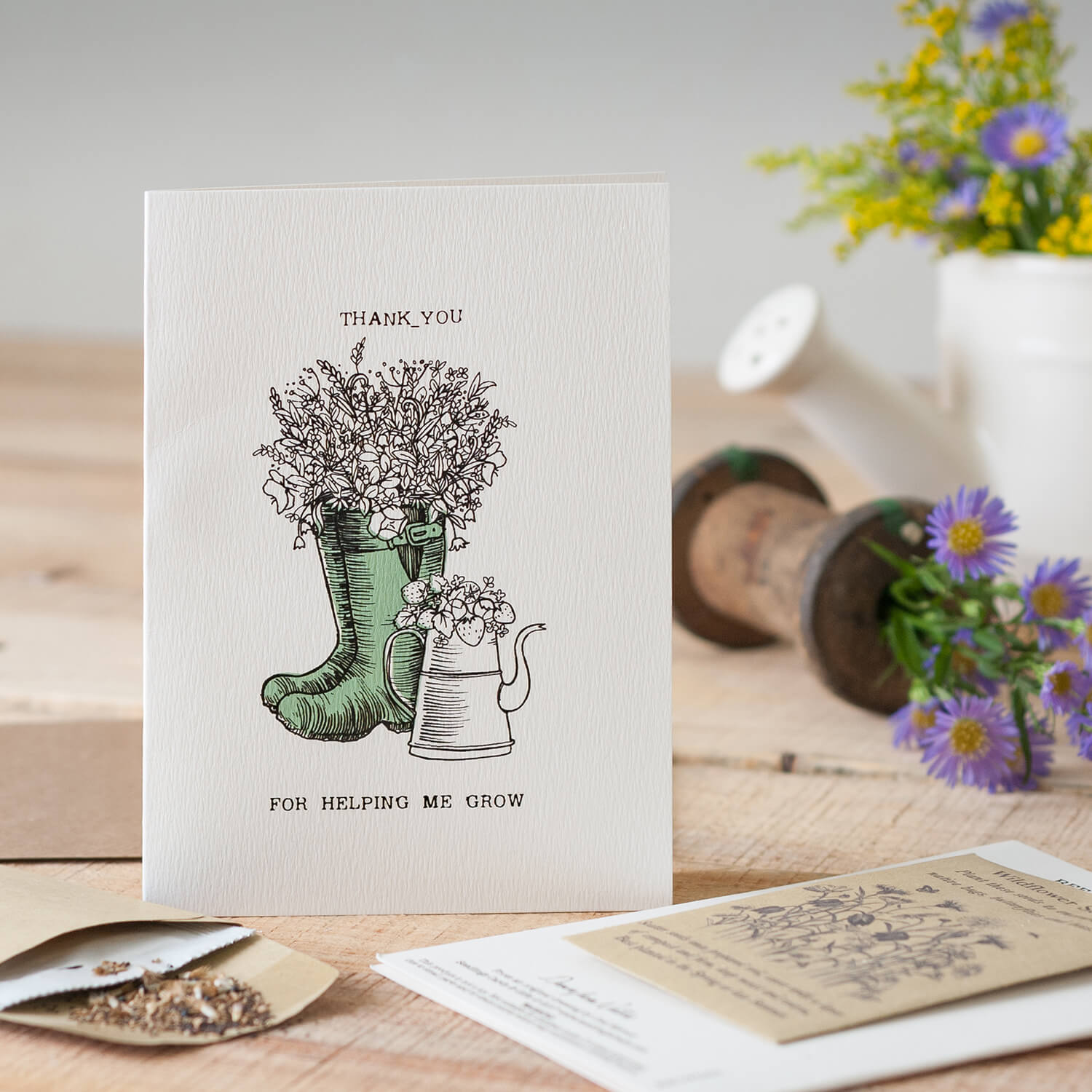 Single product photograph of a greetings card using fresh flowers and rustic items as props
