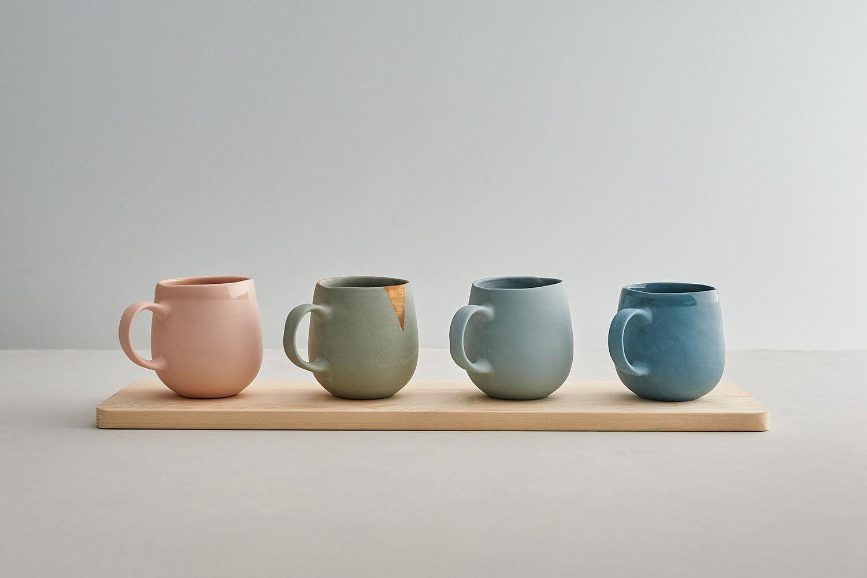 Handmade ceramics mugs photographed against subtle coloured background and surface