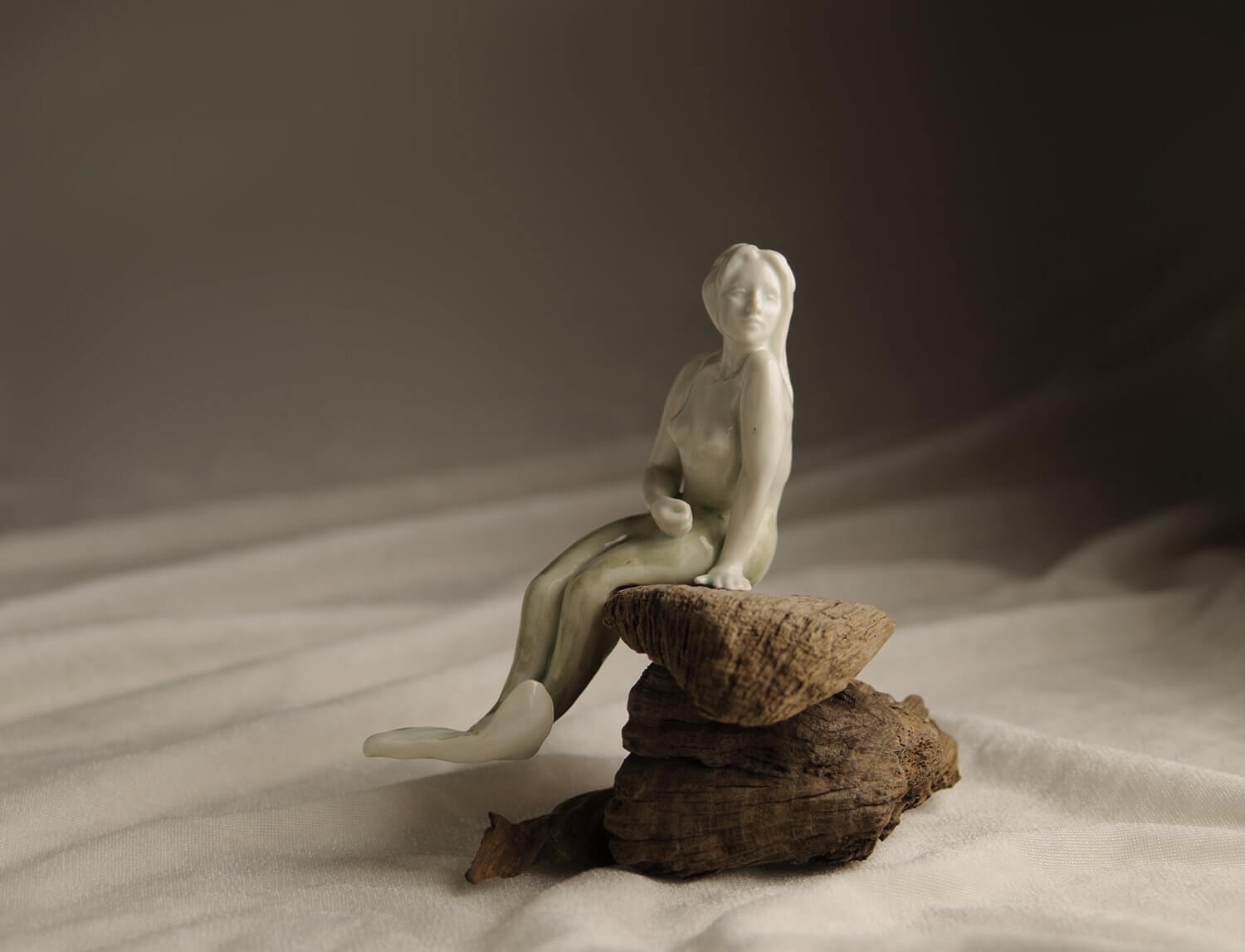 Mermaid ceramic sculpture photographed on a piece of fabric with ripples reminiscent of ocean waves