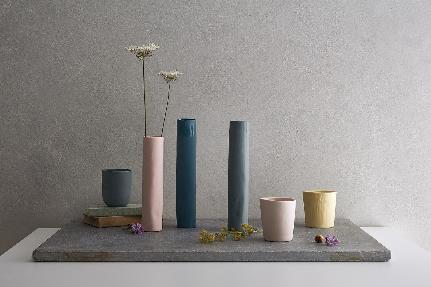 Still life composition of ceramics styled with books and wildflowers
