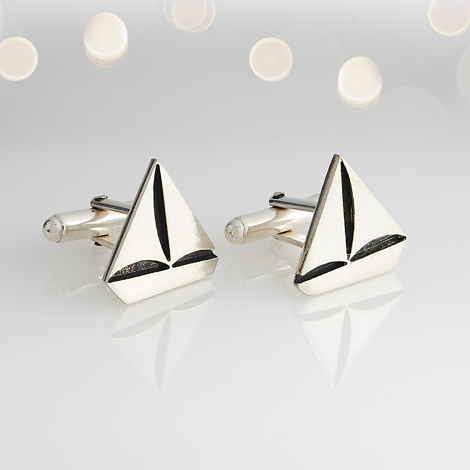 Cufflinks in the style of boats product photograph with white background and reflection