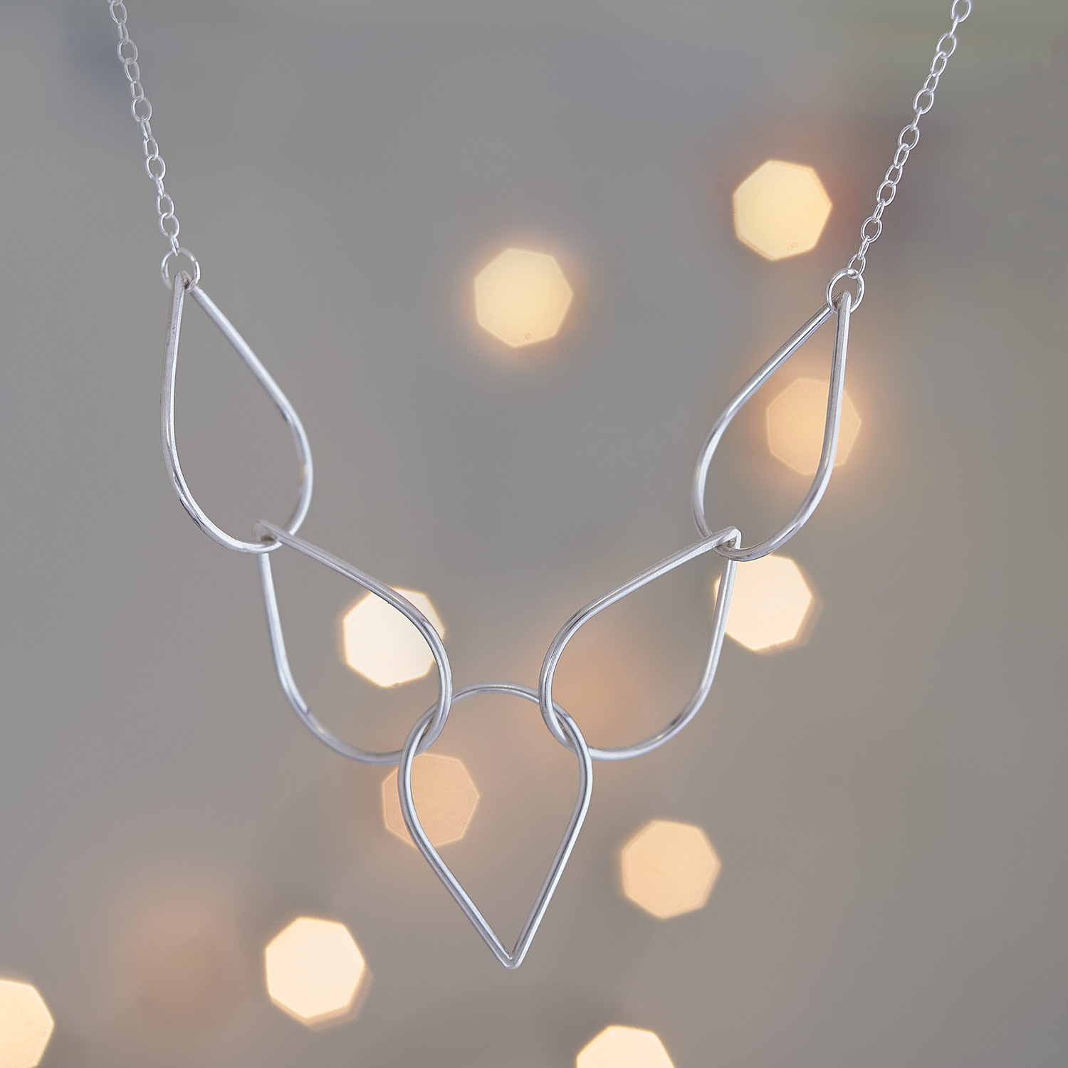 Silver necklace photograph with out of focus lights in the background