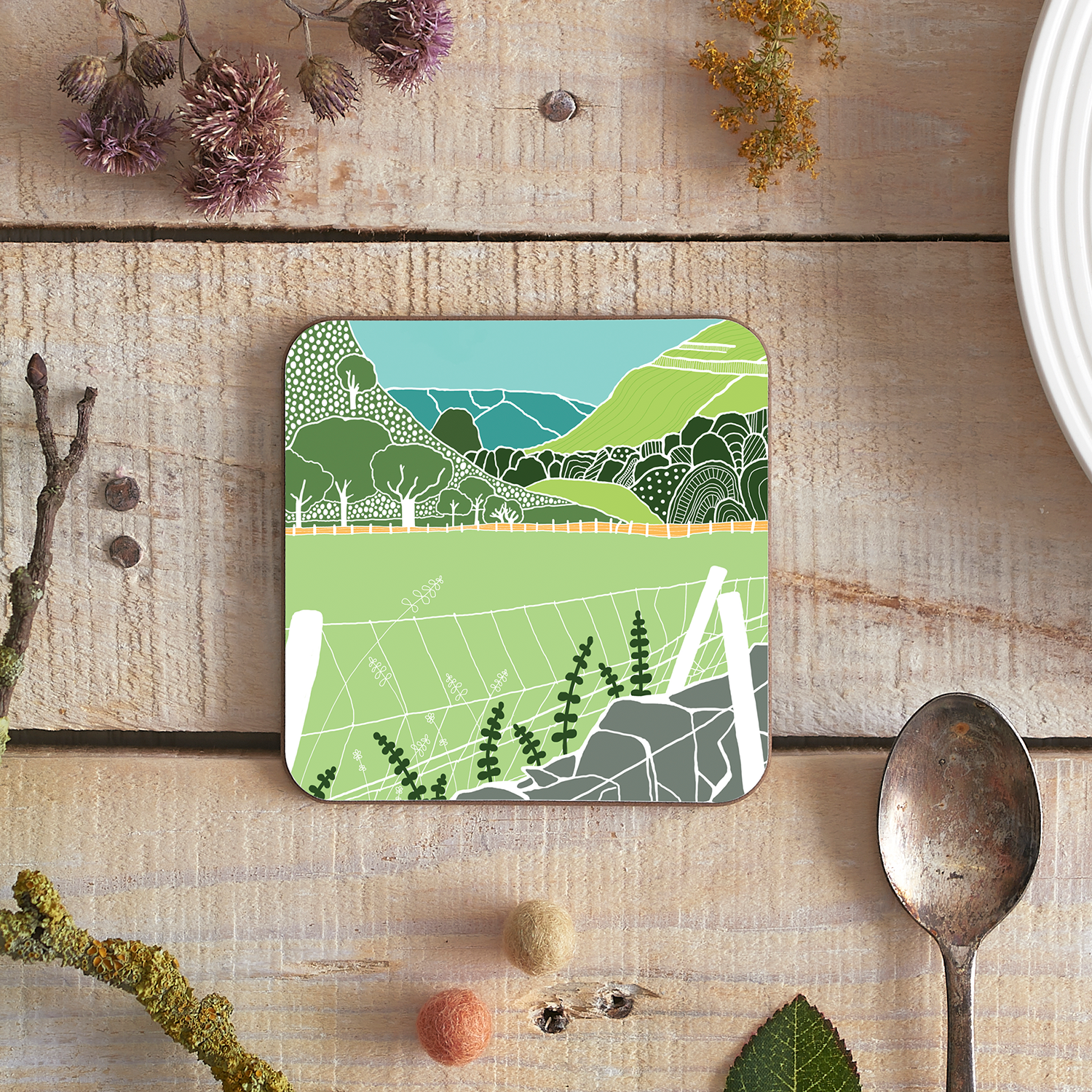 Flatlay type product photograph of a coaster featuring Lake District illustration for nature lovers