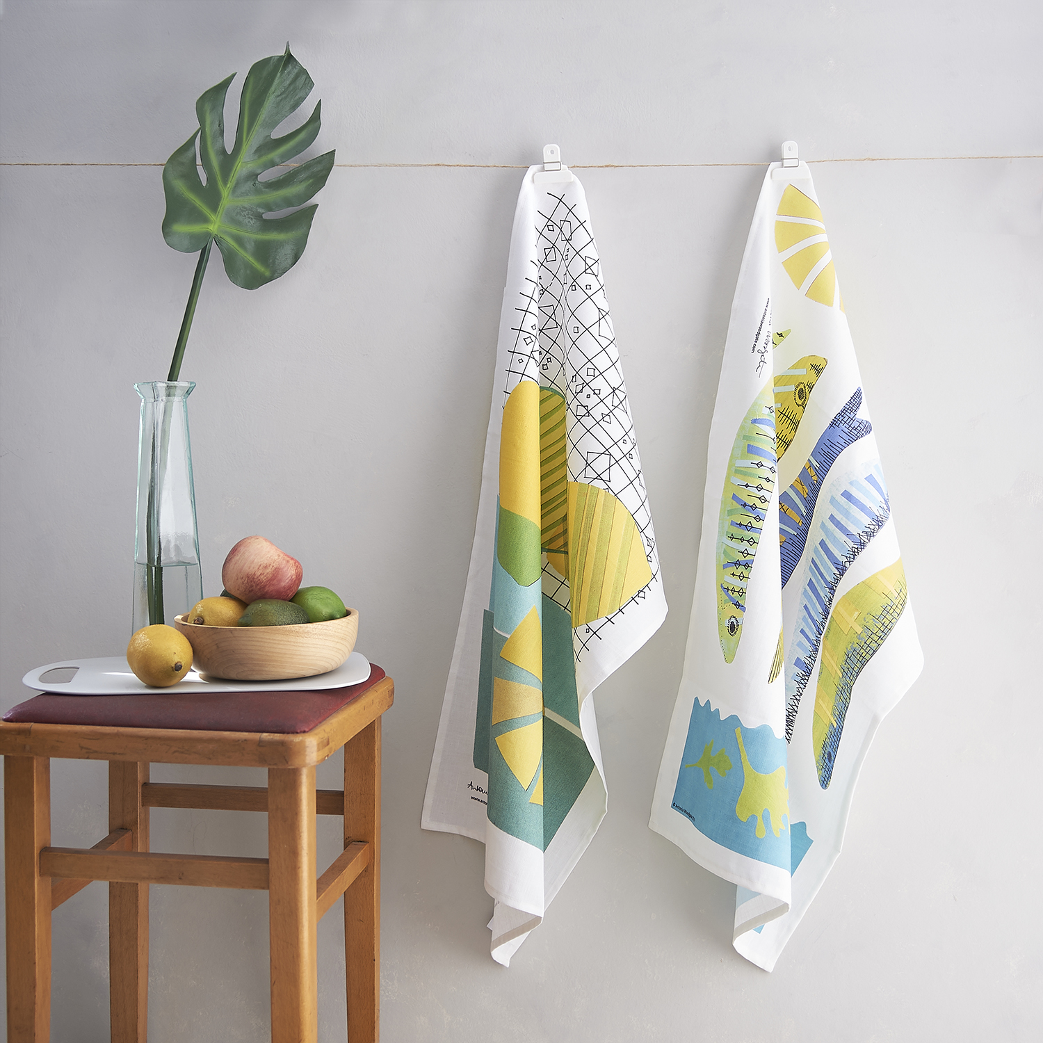 Tea towels by Antonia Woodgate in setting with mid century kitchen stool and other kitchen props