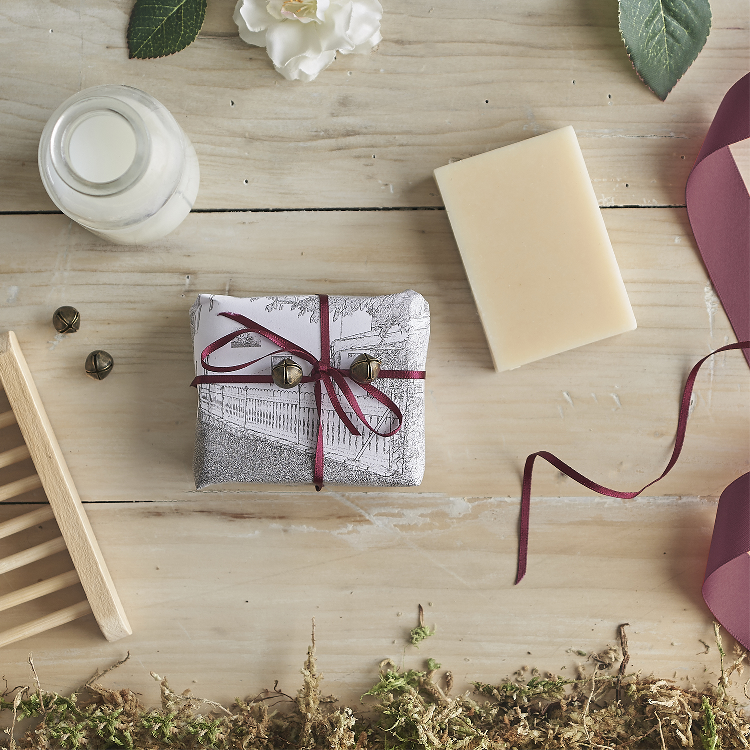 An overhead photograph of packaged handmade soap in a rustic setting